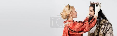 blonde queen wearing crown on hispanic king in medieval clothing isolated on white, banner