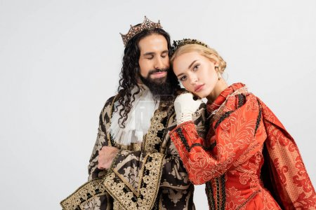 interracial king and queen in medieval clothing and crowns hugging isolated on white