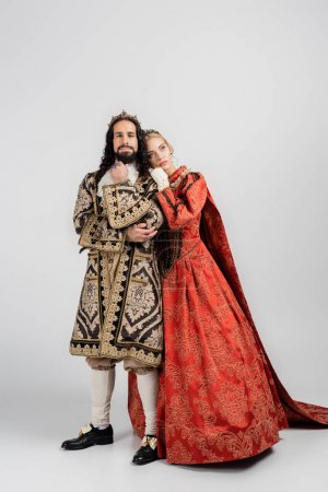 Photo for Full length of queen in royal crown leaning on hispanic king in medieval clothing on grey - Royalty Free Image