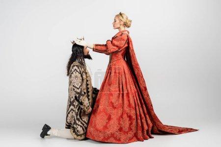Photo pour Pleine longueur de reine blonde portant la couronne sur roi hispanique en vêtements médiévaux debout sur le genou sur blanc - image libre de droit