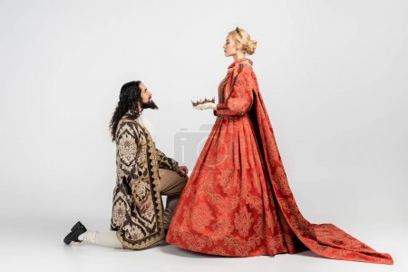 Photo for Side view of blonde queen holding crown near hispanic king in medieval clothing standing on knee on white - Royalty Free Image