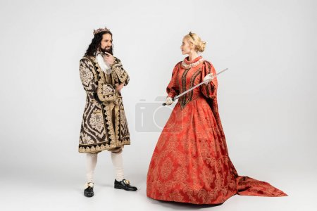 full length of blonde queen holding sword near hispanic king in medieval clothing standing on white