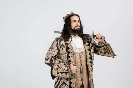 Photo for Hispanic king in medieval clothing and crown holding sword while looking away isolated on white - Royalty Free Image
