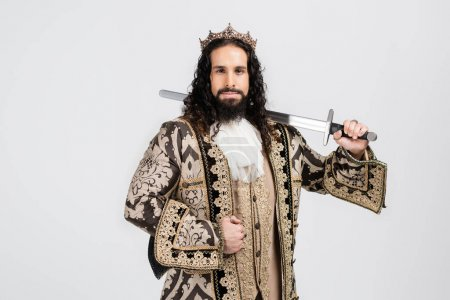 strong hispanic king in golden crown and medieval clothing holding sword while looking at camera isolated on white