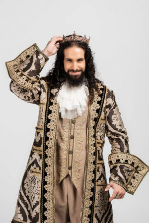smiling hispanic king in medieval clothing holding golden crown while looking at camera isolated on white
