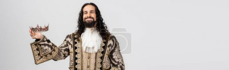 pleased hispanic king in medieval clothing holding golden crown while looking at camera isolated on white, banner