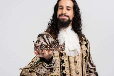 blurred hispanic king in medieval clothing holding golden crown isolated on white