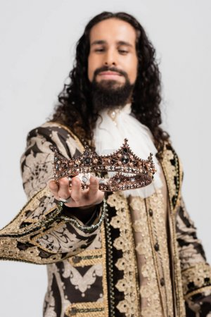 blurred hispanic king in medieval clothing holding crown isolated on white