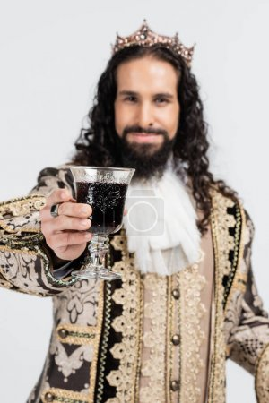 Photo for Blurred hispanic king in medieval clothing and crown holding glass of red wine isolated on white - Royalty Free Image