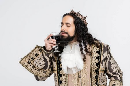 Photo for Hispanic king in medieval clothing and crown smelling glass of red wine isolated on white - Royalty Free Image