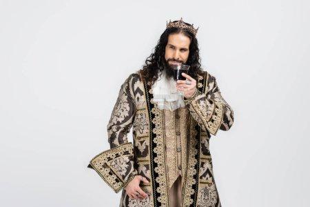 Photo pour Roi hispanique en vêtements médiévaux et couronne tenant verre avec vin rouge isolé sur blanc - image libre de droit