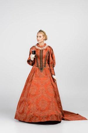 Photo pour Pleine longueur de reine en robe et couronne tenant verre de vin rouge sur blanc - image libre de droit