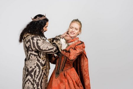 Photo for Hispanic king in medieval clothing choking queen in crown on white - Royalty Free Image