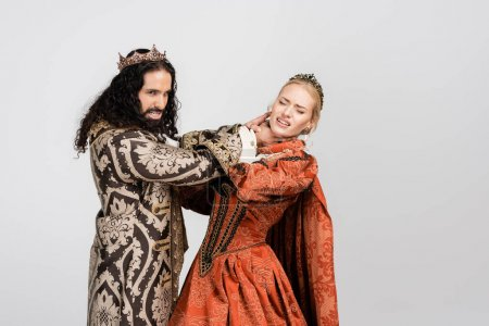 Latynoski król w średniowiecznej odzieży dławiący przestraszoną królową w koronie odizolowaną na biało