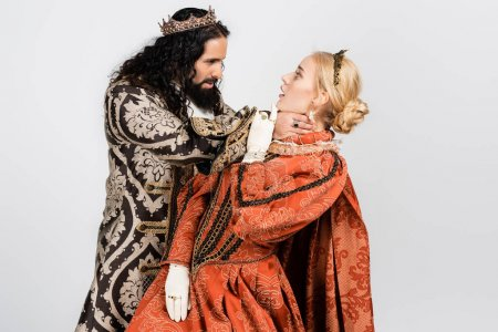 cruel hispanic king in medieval clothing choking shocked queen in golden crown isolated on white