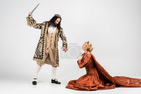Photo for Full length of hispanic king in medieval clothing holding sword near scared blonde queen in crown sitting with praying hands on white - Royalty Free Image