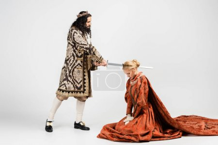 full length of cruel hispanic king in medieval clothing holding sword near scared queen in crown on white