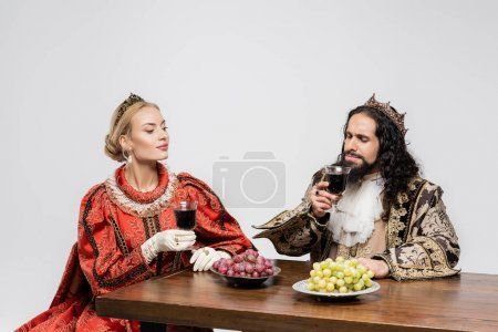 blonde queen looking at hispanic king in medieval clothing smelling red wine in glass isolated on white
