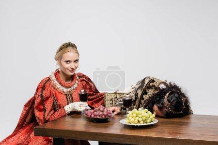 Photo pour Heureuse reine tenant verre de vin rouge près empoisonné roi hispanique dans des vêtements médiévaux isolés sur blanc - image libre de droit