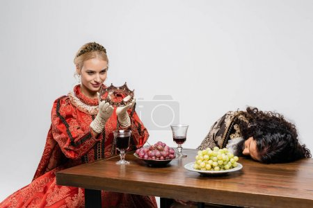 blonde queen holding crown near poisoned hispanic king in medieval clothing isolated on white