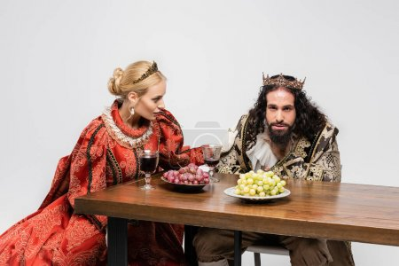blonde queen looking at poisoned hispanic king in medieval clothing choking isolated on white