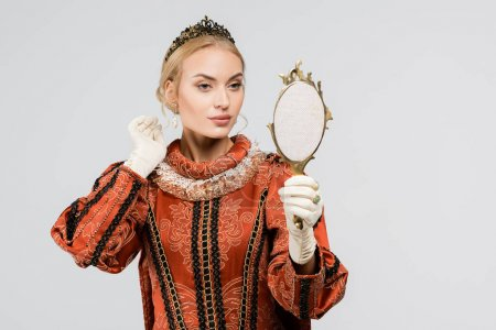 blonde queen in crown looking at mirror isolated on white