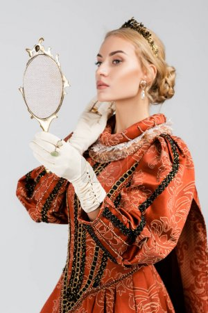 blonde queen in dress and crown looking at mirror isolated on white