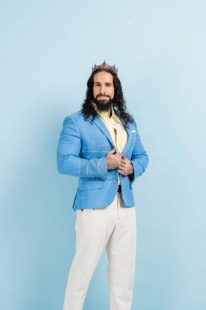 bearded hispanic man in crown and jacket posing on blue
