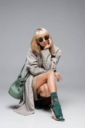 full length of stylish young woman in sunglasses and trench coat posing with green bag on grey