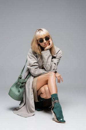 Photo for Full length of stylish young woman in sunglasses and trench coat posing with green bag on grey - Royalty Free Image