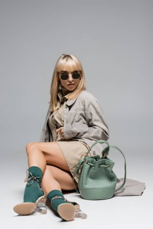 full length of trendy woman in sunglasses and trench coat posing with bag on grey