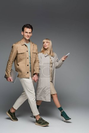 Photo for Full length of trendy couple holding hands while walking with gadgets on grey - Royalty Free Image