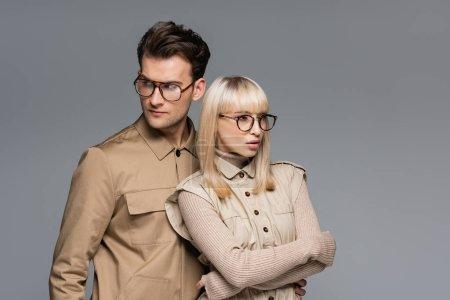 Photo pour Jeunes modèles à la mode dans des lunettes posant isolé sur gris - image libre de droit