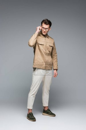 full length of trendy man in stylish outfit posing while adjusting glasses on grey