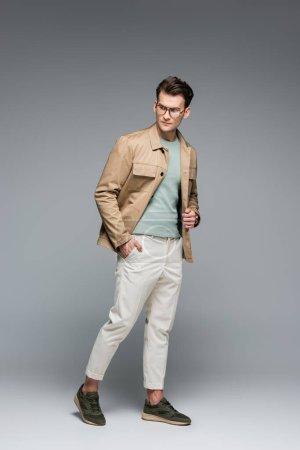 volle Länge der stilvolle Mann posiert mit der Hand in der Tasche auf grau