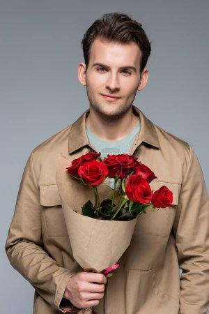 Lächelnder Mann mit einem Strauß roter Rosen auf grauem Grund