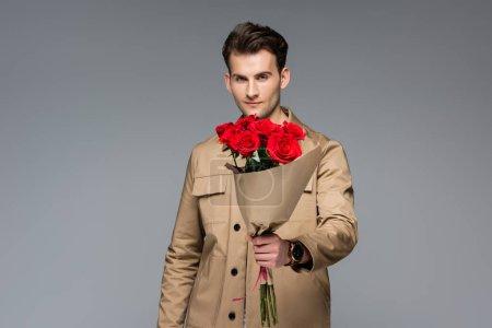 Photo pour Élégant homme tenant bouquet de roses rouges isolé sur gris - image libre de droit