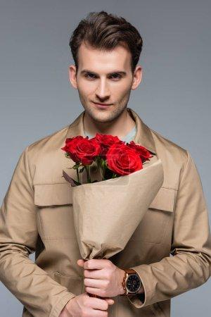 Photo pour Élégant homme tenant bouquet de roses rouges enveloppé dans du papier isolé sur gris - image libre de droit
