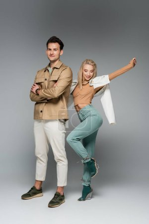 full length of stylish models in pants and jackets posing and smiling on grey