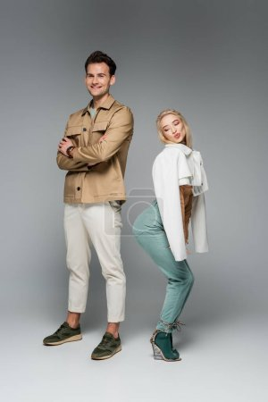 Photo for Full length of happy models in pants and jackets posing and smiling on grey - Royalty Free Image