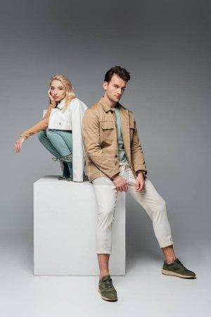 Photo pour Toute la longueur des modèles élégants en pantalon et vestes posant tout en étant assis sur cube blanc sur gris - image libre de droit