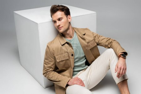 trendy man posing while leaning on white cube on grey