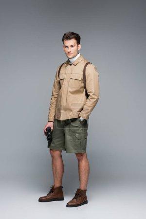 Photo pour Toute la longueur du voyageur branché en short et veste debout avec la main dans la poche tout en tenant des jumelles sur le gris - image libre de droit