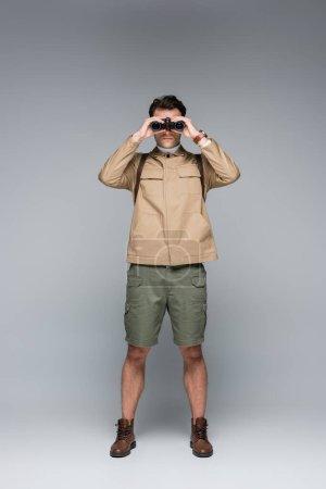 Photo pour Toute la longueur du voyageur à la mode en short et veste regardant à travers les jumelles sur gris - image libre de droit