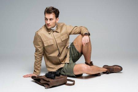 Photo pour Sur toute la longueur du voyageur branché en short et veste assis près du sac à dos en cuir avec jumelles sur gris - image libre de droit