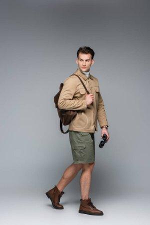 Photo pour Sur toute la longueur du voyageur branché en short et veste de marche avec jumelles sur gris - image libre de droit
