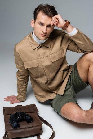 Photo pour Voyageur branché en short et veste assis près du sac à dos en cuir avec jumelles sur gris - image libre de droit