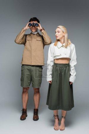 Photo pour Pleine longueur de voyageur à la mode regardant à travers les jumelles près de femme blonde sur gris - image libre de droit