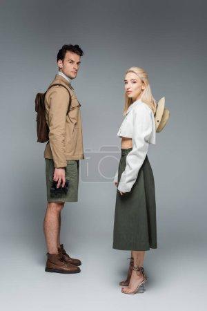 Photo pour Toute la longueur des voyageurs à la mode en tenue élégante debout sur le gris - image libre de droit