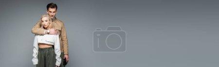Photo pour Homme à la mode tenant des jumelles et étreignant femme blonde isolée sur gris, bannière - image libre de droit